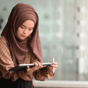 A woman openly wears a hijab while working on a tablet as her workplace has guidelines to help accomodate her religious beliefs