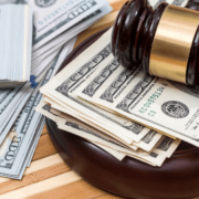 A gavel rests on top of money, signifying the monetary caps on lawsuits